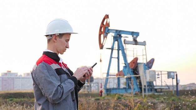 Uomo in un casco bianco con un telefono sullo sfondo di un dondolo in un pozzo di petrolio