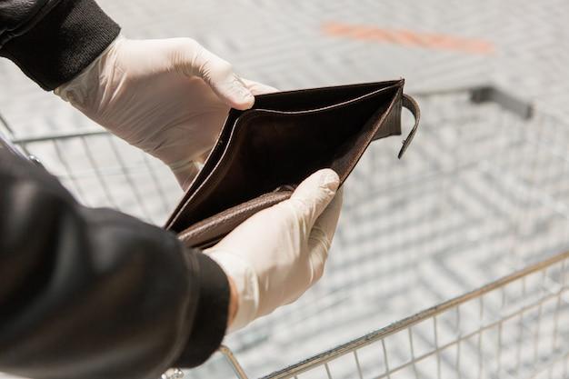 Uomo in guanti bianchi del lattice che tengono borsa vuota. borsa marrone senza soldi. problemi finanziari