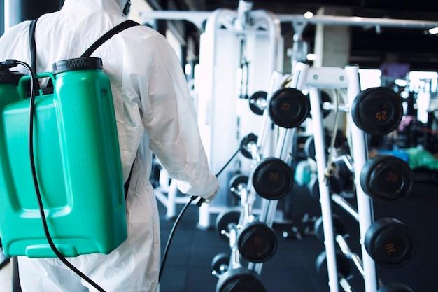 Uomo in tuta di protezione bianca che disinfetta e attrezzature per il fitness e pesi per fermare la diffusione del virus corona altamente contagioso.