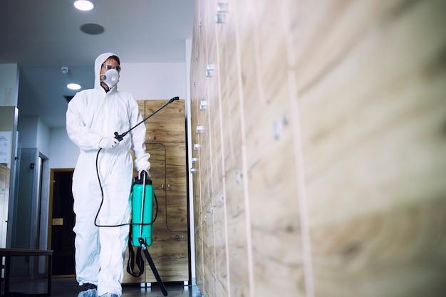 Uomo in tuta di protezione bianca che disinfetta e igienizza gli armadietti nel camerino della palestra per fermare la diffusione del virus corona altamente contagioso.
