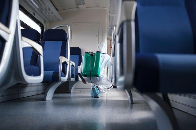Uomo in tuta di protezione bianca che disinfetta e igienizza l'interno del treno della metropolitana per fermare la diffusione del virus corona altamente contagioso.
