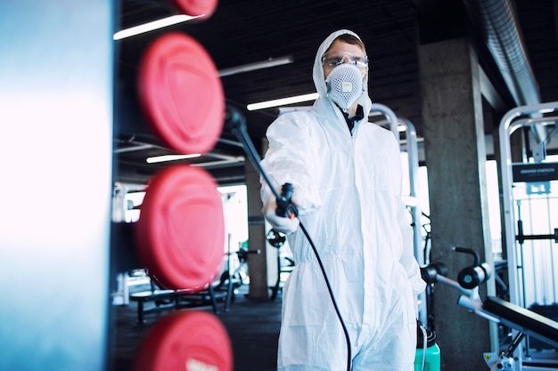 Uomo in tuta di protezione bianca che disinfetta e spruzza un set di pesi per fermare la diffusione del virus corona altamente contagioso.