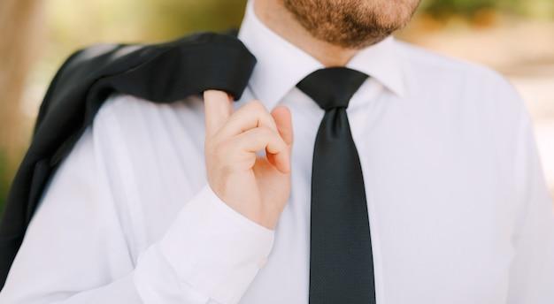 Un uomo in camicia bianca e cravatta nera si leva in piedi e tiene una giacca sopra il suo primo piano della spalla