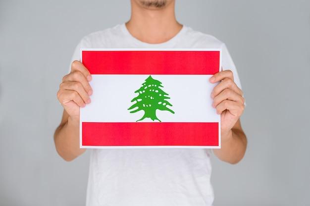 Uomo in una camicia bianca che tiene la bandiera del libano.