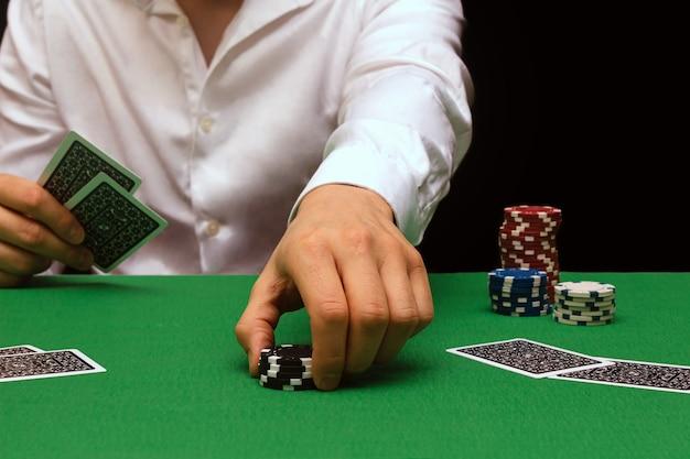 Un uomo con una camicia bianca gioca a poker in un'attività di gioco d'azzardo in un casinò. industria dei locali notturni. molti soldi. affari di poker online. copia spazio