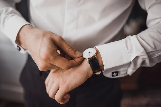 Uomo in una camicia bianca raddrizza il suo orologio