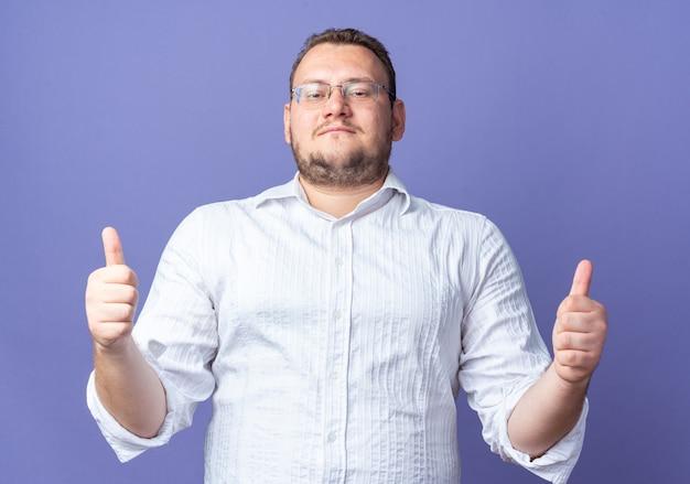 Uomo in camicia bianca con gli occhiali sorridenti felici e positivi che mostrano i pollici in su in piedi sul muro blu