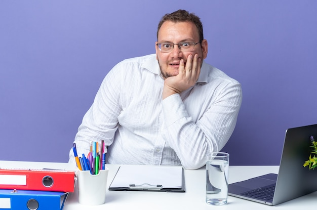 Uomo in camicia bianca con gli occhiali felice e sorpreso seduto al tavolo con laptop e cartelle per ufficio sul muro blu che lavora in ufficio