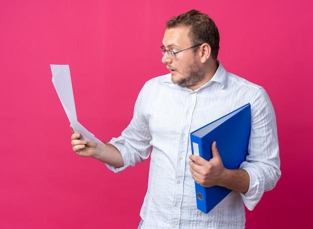 Uomo in camicia bianca con gli occhiali che tiene in mano la cartella dell'ufficio e i documenti che li guardano stupiti e sorpresi in piedi sul rosa
