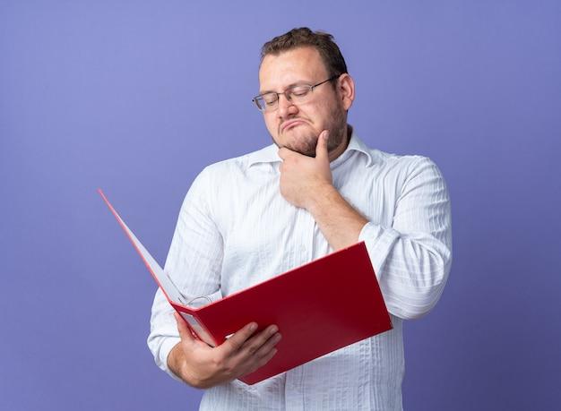 Uomo in camicia bianca con gli occhiali che tiene la cartella dell'ufficio guardandola con espressione pensosa con la mano sul mento in piedi sul muro blu