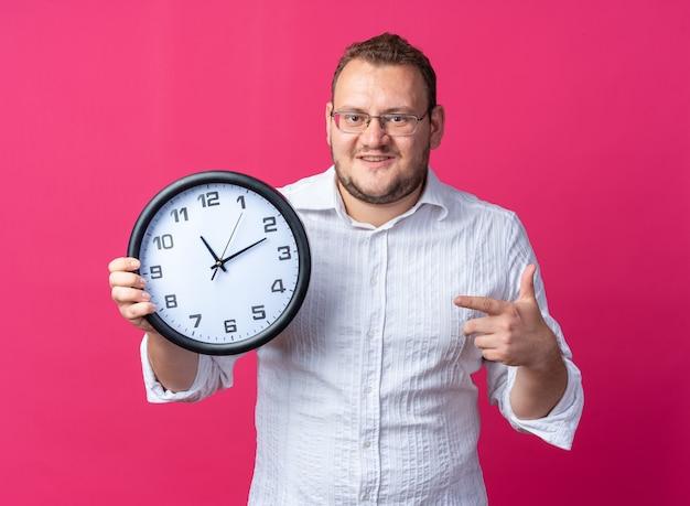 Uomo in camicia bianca con gli occhiali che tiene l'orologio da parete che punta con il dito indice e sembra sorridente felice e allegro