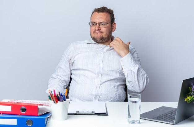 Uomo in camicia bianca con gli occhiali che guarda da parte infastidito e irritato toccando il suo colletto seduto al tavolo con cartelle per ufficio portatile e appunti su bianco