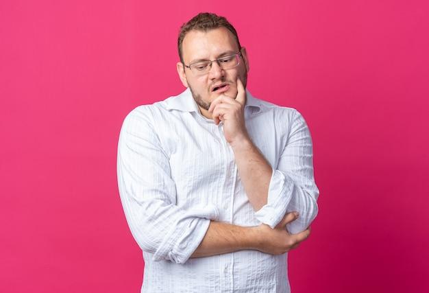 Uomo in camicia bianca con gli occhiali che guarda in basso perplesso in piedi sul rosa