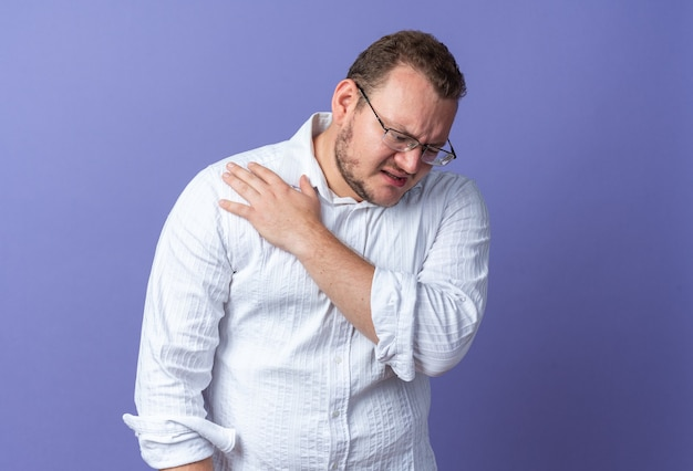 Uomo in camicia bianca con gli occhiali che sembra indisposto toccandosi la spalla sentendo dolore in piedi sul muro blu