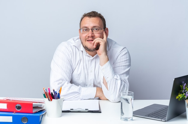 Uomo in camicia bianca con gli occhiali guardando in alto pensare positivo sorridente seduto al tavolo con laptop cartelle per ufficio e appunti sul muro bianco lavorando in ufficio