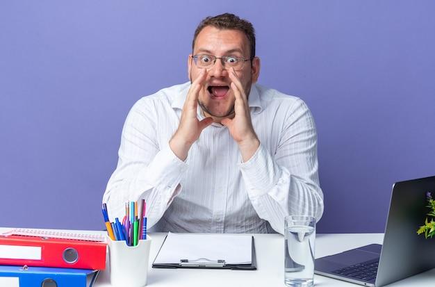 Uomo in camicia bianca con gli occhiali che grida con le mani sopra la testa essendo felice ed eccitato grida seduto al tavolo con laptop e cartelle per ufficio su sfondo blu che lavora in ufficio