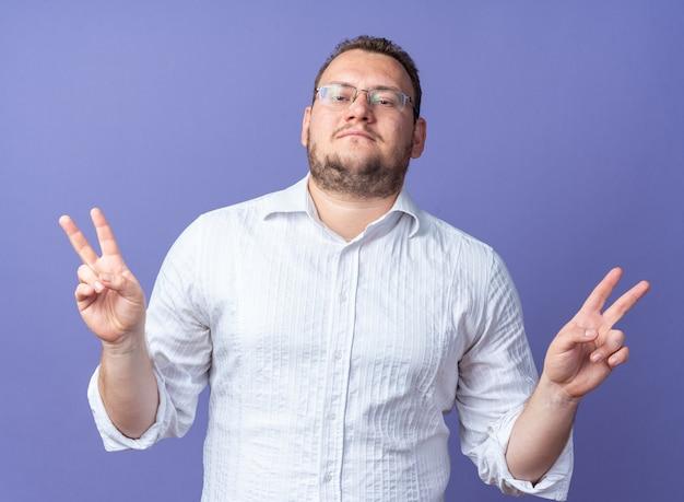 Uomo in camicia bianca con gli occhiali sorridente fiducioso che mostra il v-sign in piedi sul muro blu
