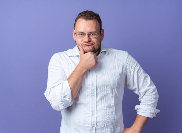 Uomo in camicia bianca con gli occhiali con la mano sul mento che pensa con un'espressione pensierosa in piedi sul muro blu