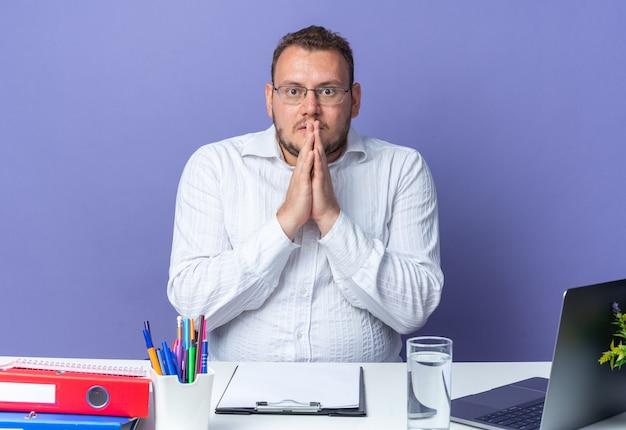 Uomo in camicia bianca con gli occhiali con le mani unite stressato e nervoso seduto al tavolo con laptop e cartelle per ufficio sul muro blu che lavora in ufficio