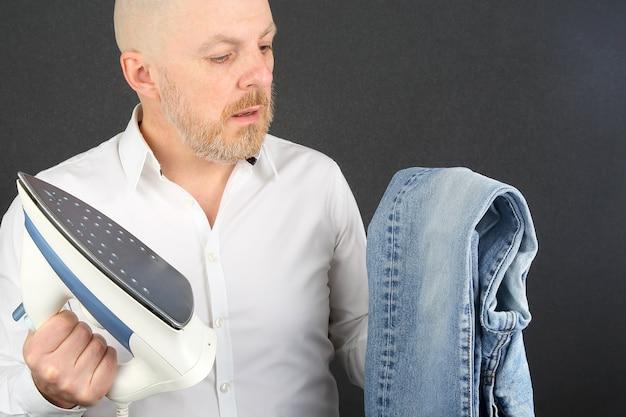 Uomo in una camicia bianca con un ferro da stiro e jeans nelle sue mani