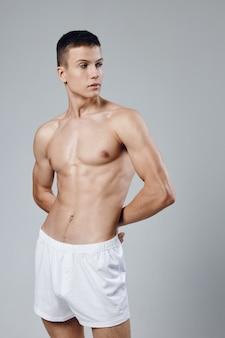 Un uomo in pantaloncini bianchi tiene le mani dietro la schiena uno sguardo all'allenamento del busto gonfiato laterale.