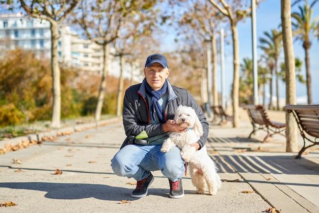 Parco della passeggiata del cane di piccola taglia dell'uomo bianco