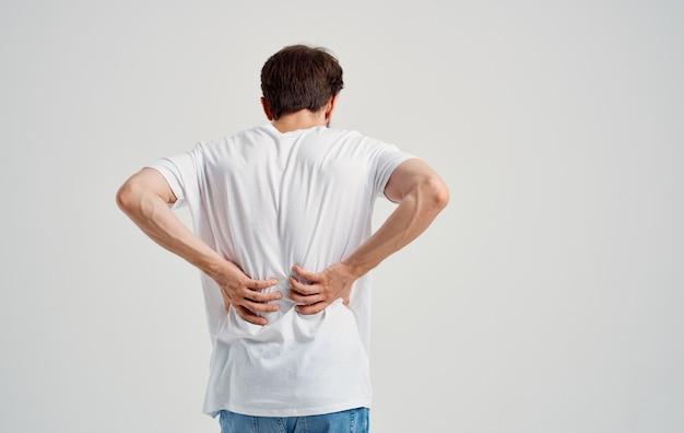 Uomo in t-shirt bianca dolore alla schiena osteocondrosi della colonna vertebrale modello vista posteriore