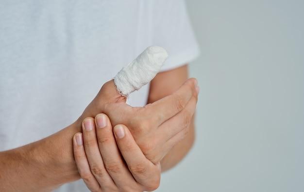 Uomo in maglietta bianca bendata medicina problemi di salute del pollice