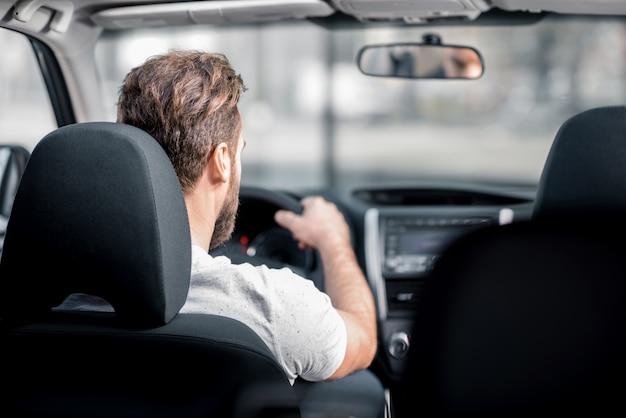 Uomo in maglietta bianca alla guida di un'auto in città. vista posteriore