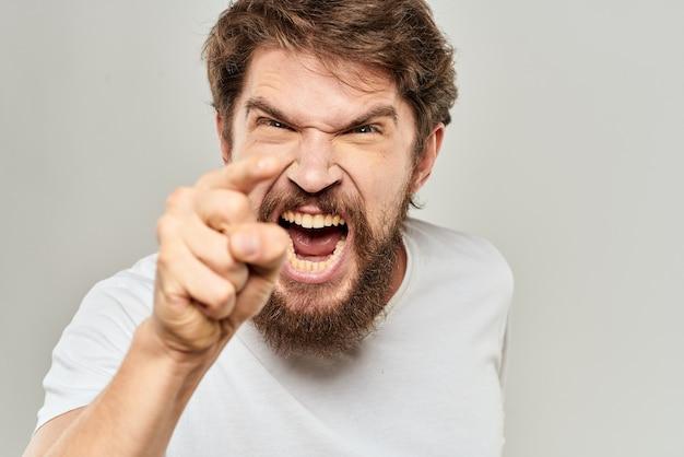 Uomo in t-shirt bianca emozioni espressioni gesto con le mani sfondo chiaro