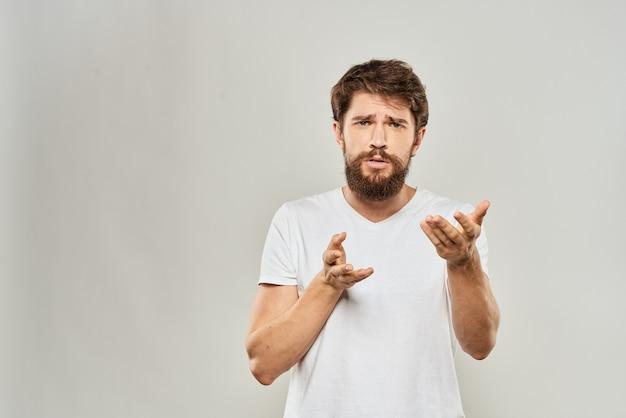 Uomo in maglietta bianca che gesturing con la sua luce di lifestyle di insoddisfazione dello studio delle mani.