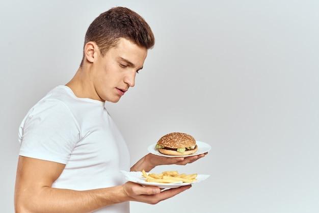 Uomo in t-shirt bianca hamburger patatine fritte fast food snack. foto di alta qualità