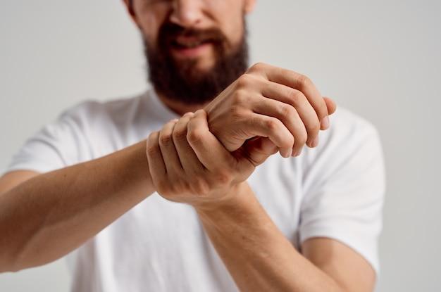 Uomo in maglietta bianca infortunio alla mano problemi di salute dolori articolari. foto di alta qualità