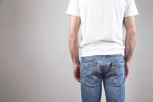 Uomo in una maglietta bianca e jeans.