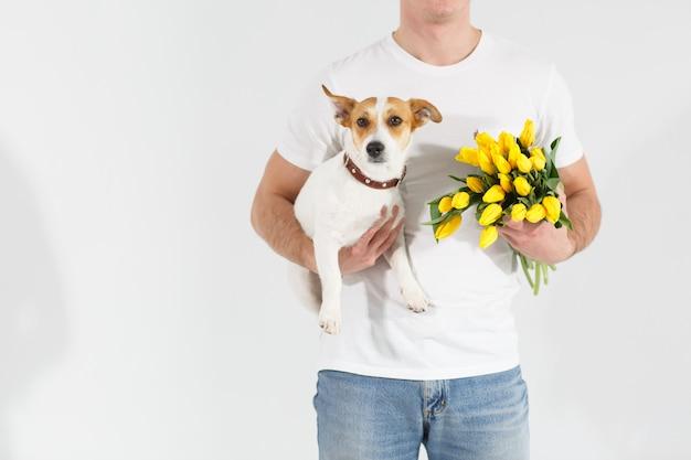 Uomo in maglietta bianca che sta con i fiori e il cane.