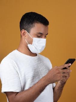 Uomo in maglietta bianca che indossa la maschera con il cellulare nelle sue mani