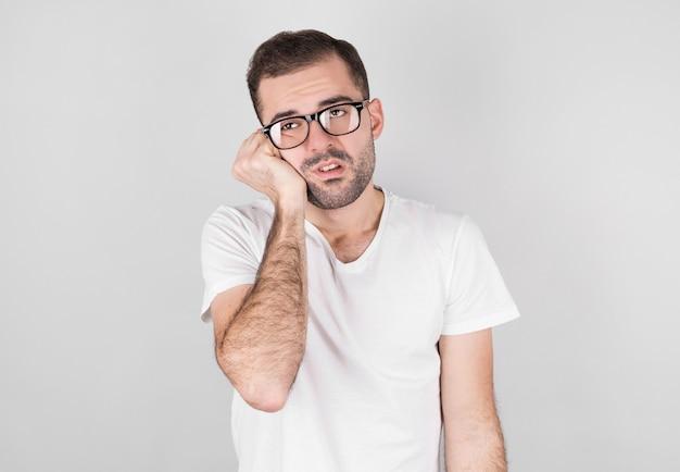 L'uomo in una maglietta bianca con una bella barba sembra stanco di lato.