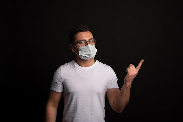 Uomo in maglietta bianca con maschera usa e getta. protezione contro virus e infezioni.