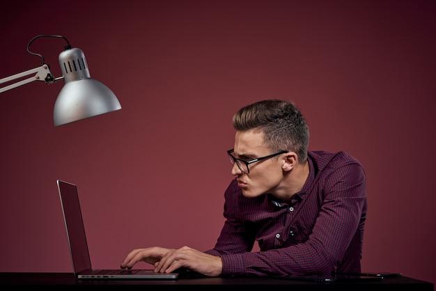 Un uomo in una maglietta bianca con un computer portatile e una tavoletta elettronica lavora al tavolo