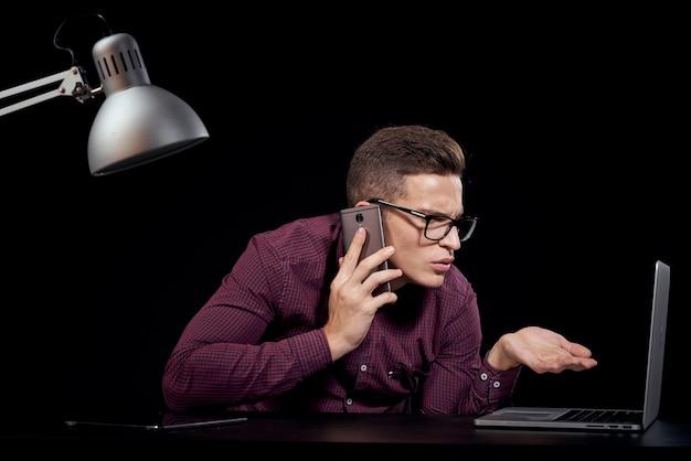 L'uomo in una maglietta bianca con un computer portatile e una tavoletta elettronica lavora al tavolo