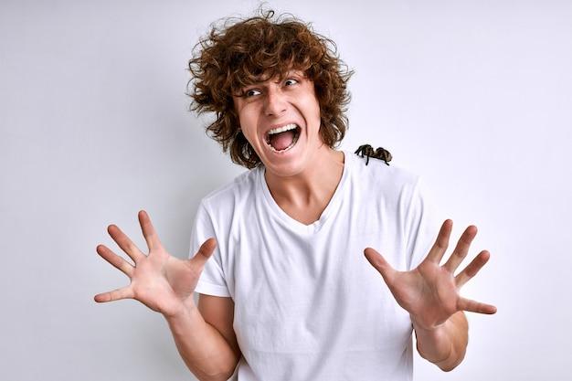 Uomo in una maglietta bianca con ragno su un muro bianco, maschio sta urlando, spaventato, paura di aracnofobia dei ragni