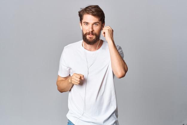 Un uomo con una maglietta bianca fa gesti con le sue mani emozioni movimento studio sfondo chiaro