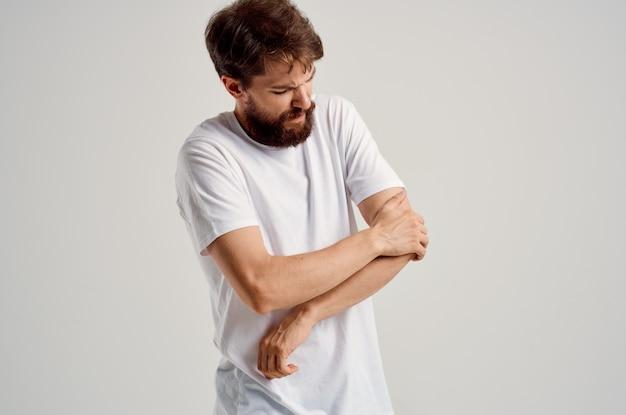 Uomo in maglietta bianca infortunio alla mano problemi di salute dolori articolari