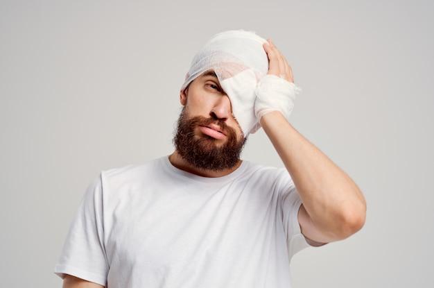 L'uomo con una maglietta bianca ha un trattamento per la diagnosi della salute del trauma