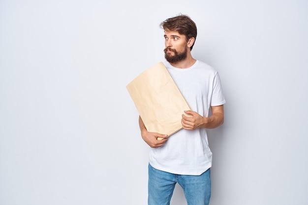 Un uomo con una maglietta bianca con un sacchetto di carta in mano su uno sfondo chiaro