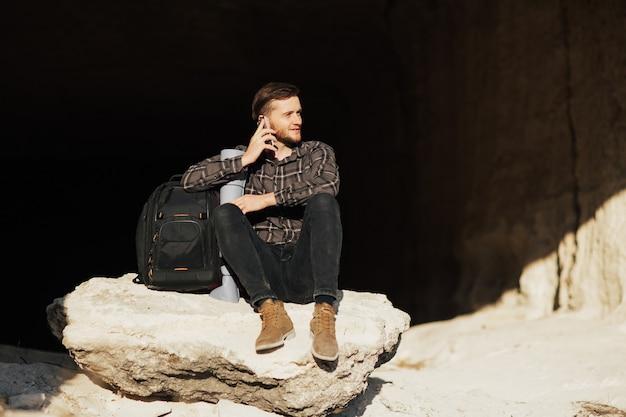 Uomo che siede sulla pietra della montagna e parla al telefono