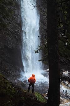 Uomo in giacca a vento in piedi vicino alle cascate di plodda, scozia