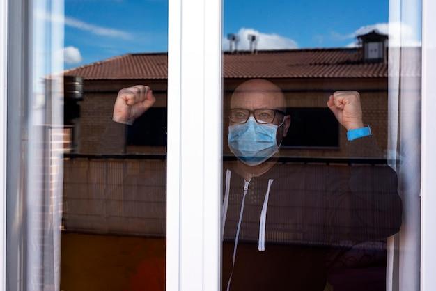 Uomo dietro una finestra con una maschera e colpire la finestra