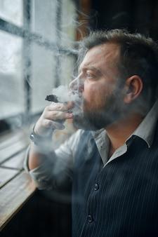 Uomo al davanzale della finestra e fuma un sigaro, interni ufficio vintage. cultura del fumo di tabacco, sapore specifico. il fumatore maschio guarda la finestra