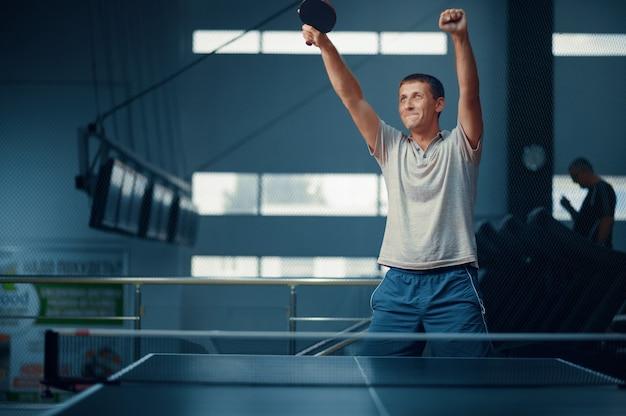L'uomo vince la partita di tennis da tavolo
